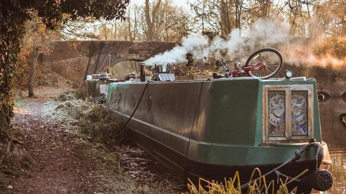 How much does it cost to live on a canal boat - green narrowboat next to the towpath